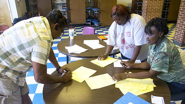 DAILY LEADER / KATIE WILLIAMSON / Sherry Course, (from left) Juana Dixon and Argie Dixon count votes in the city election on the lodging tax at the Ward Six precinct at Mamie Martin Elementary School Tuesday night.