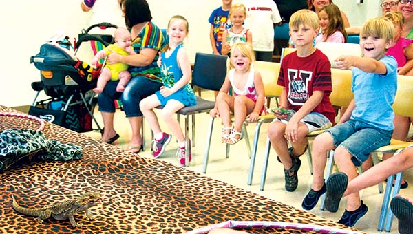 """Emma Bower, 6; Zayleigh Rippy, 2; Zander Rippy, 8; and Zad Rippy watch as a lizard eats a cricket. Thursday's visit from the ZooMobile was part of July's """"Fizz, Boom, Read"""" program at the library."""