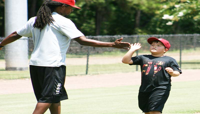 DAILY LEADER / MARTY ALBRIGHT / Josh Sandifer (right) gives camp director Nook Logan a high-five after rounding third base in the three-day baseball clinic.