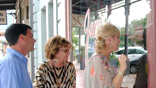 DAILY LEADER / LYNDY BERRYHILL / The Brookhaven-Lincoln County Chamber of Commerce's Garrick Combs, (from left) Pam Cartwright and Kay Burton look through the windows of Janie's Pastry Shop & Bakery Thursday. Shooting for the movie, The Hollars, is set to begin inside the shop late this week.