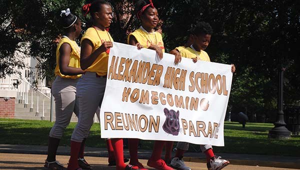 DAILY LEADER / JULIA PENDELY / Jamyria James, Shantraille Haynes and Tommya Crossley lead the way with a banner for the Alexander High School graduates. The parade was part of a weekend-long series of reunion events, which concluded today with a worship service and a farewell dinner.