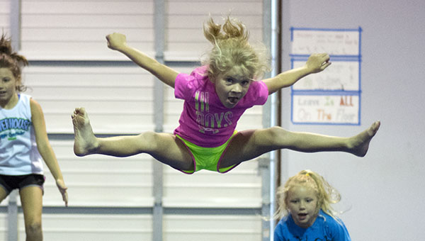 DAILY LEADER / KATIE WILLIAMSON / Taylor Douglas, 7 practices her toe touches during Powerhouse Cheer Camp at the Brookhaven Parks and Recreation Department Monday. The cheer camp is just one of many activities held for children during the summer at the recreation department. For more information, contact the department at (601) 833-3791 or visit the website at http://www.brookhavenrecreation.com/