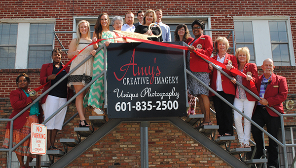 DAILY LEADER / LYNDY BERRYHILL / NEW LOCATION - Amy's Creative Imagery celebrated the move to their new location 203 E. Monticello Street with a ribbon cutting Thursday at the new studio. Amy Rhoads, photographer, specializes in senior, wedding and family portraits as well as graduation invitations. Rhoads shoots portraits in studio and on location. Studio hours are from 10 a.m. until 5 p.m. and by appointment. Present for the ceremony were (from left) Donna Foster, Cynthia Price, Kaitlyn Rhoads, Megyn Rhoads, Elsie Smith, Garland Boyd, Amy Rhoads, Dustin Walker, Wendy Smith, Brenda Henderson, Imogene Ryan, Sheila Burd and Kim Bridge.