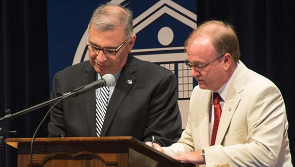 DAILY LEADER / KATIE WILLIAMSON / Mississippi University for Women President Jim Borsig and Copiah-Lincoln Community College President Ronnie Nettles sign a memorandum of agreement Thursday in Rea Auditorium on Co-Lin's Wesson campus.