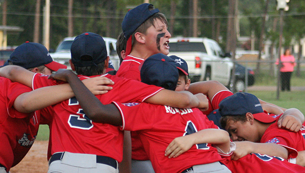 DAILY LEADER / MARTY ALBRIGHT / The Lincoln County Americans 12-year-old Majors huddle in celebration after clinching the final spot to advance to the State Tournament next week. Lincoln County defeated Pine Hill 7-4 Wednesday night at Keystone Park.