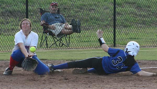Brookhaven Academy K.K. Jordan (33) slides into third base safely as Simpson Academy third baseman Annie Maddox prepares to make the play Friday night.