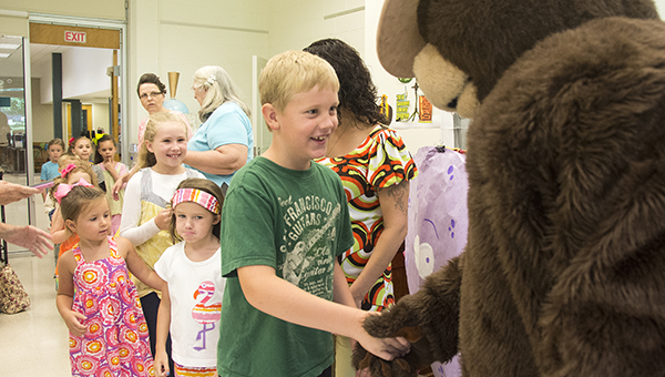 DAILY LEADER / KATIE WILLIAMSON / Baylor Sills, 8 is the first to shake the hand of Smokey Bear on his 70th birthday at the Lincoln-Lawrence-Franklin Regional Library on Tuesday.